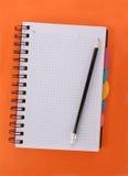 笔记本桔子铅笔 库存照片