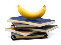 笔记本用在与裁减路线的白色背景安置的香蕉 免版税库存照片
