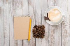 笔记本用铅笔下份咖啡和咖啡豆,巧克力片断在木背景的 安置文本 顶视图 免版税库存照片