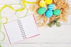 笔记本用eco在巢的复活节彩蛋在土气白色背景 图库摄影