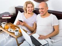 从笔记本的成熟微笑的夫妇读书新闻 库存照片