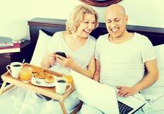 从笔记本的成熟正面微笑的夫妇读书新闻 库存图片