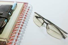 笔记本笔和玻璃 免版税库存图片