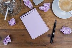 笔记本笔咖啡烟灰缸香烟弄皱了在木桌上的纸 免版税库存图片