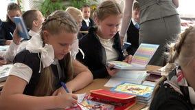 笔记本课本笔匣笔和铅笔在书桌上在学生前面在教室 股票视频