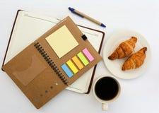 笔记本顶视图有一杯咖啡的和新月形面包 库存图片