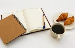 笔记本顶视图有一杯咖啡的和新月形面包 免版税库存图片