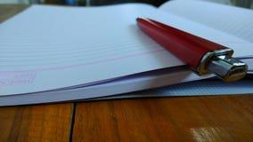 笔记本,在木背景的笔 库存照片