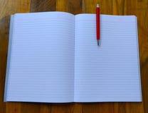 笔记本,在木背景的笔 免版税库存照片