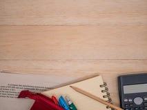 笔记本,木铅笔,固定式,计算器和数学学习在米黄木背景的活页练习题 图库摄影