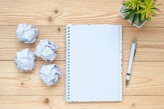 笔记本,被粉碎的纸,笔和在桌上 新年开始,创造性,想法、决议、解答、战略和使命 库存照片