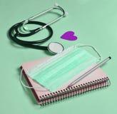 笔记本,铅笔,听诊器,在一蓝色backgr的装饰心脏 免版税库存图片