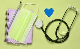 笔记本,铅笔,听诊器,在一蓝色backgr的装饰心脏 库存照片