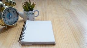 笔记本,闹钟,在木板的花瓶 库存图片