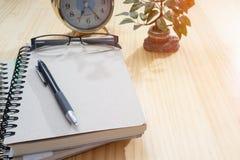 笔记本,闹钟,在木板的花瓶 免版税库存照片