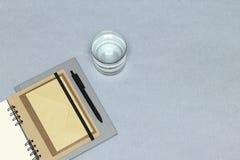 笔记本,黑笔,信封,杯在灰色背景的水 库存图片