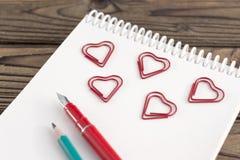 笔记本 心脏形状,铅笔,在木背景的笔 库存图片