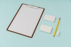 笔记板、纸、铅笔和名片在蓝色背景 图库摄影