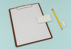 笔记板、纸、铅笔和名片在蓝色背景 免版税库存照片