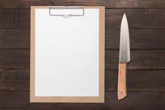 笔记板和刀子在木背景设置了 免版税库存图片