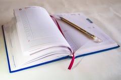 笔记的一个笔记本 与书签的书 圆珠笔 免版税库存图片