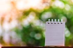 笔记的纸关于使用墙纸或背景的木头和bokeh背景 免版税库存照片