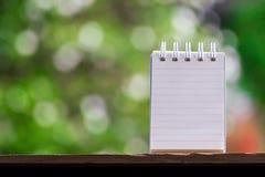 笔记的纸关于使用墙纸或背景的木头和bokeh背景 免版税库存图片