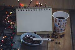 笔记薄、一块玻璃和咖啡豆在bowlnn 免版税库存照片