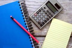 笔记薄、笔记本、计算器和一支五颜六色的铅笔 图库摄影