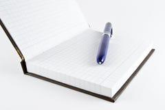 笔记薄、第一页和圆珠笔 免版税库存图片