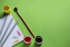 笔记薄、色的铅笔和刷子,色纸在绿色背景截去,回到学校 免版税库存图片