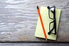 笔记薄、镜片和一支五颜六色的铅笔 免版税库存图片
