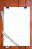 笔记薄、统治者和笔在书桌上 免版税库存图片