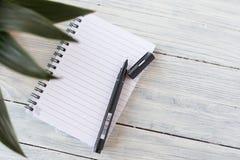 笔记薄和笔在白色木背景与一朵绿色花 图库摄影