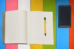 笔记薄和笔对 在桌上的智能手机 免版税库存图片