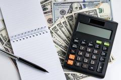笔记薄和笔,在堆的计算器美元钞票使用  免版税图库摄影