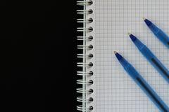 笔记薄摆正了与教育的,事务三支蓝色笔有在黑背景的拷贝空间顶视图 免版税库存图片
