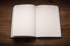 笔记薄白页在木桌上的 免版税库存图片