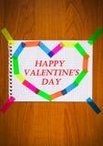 笔记薄纸愉快的华伦泰` s天题字红颜色卡片板料在心脏形状的在木背景 免版税库存照片
