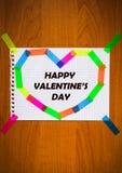 笔记薄纸愉快的华伦泰` s天题字黑色颜色卡片板料在心脏形状的在木背景 免版税库存图片