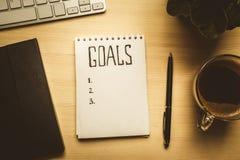 笔记薄顶视图与目标的列出,咖啡在木桌,目标概念上的 免版税库存图片