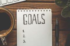 笔记薄顶视图与目标的列出,咖啡在木桌,目标概念上的 库存照片