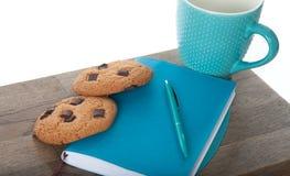 笔记薄,杯子,在绿松石颜色的笔用巧克力曲奇饼 木桌和白色背景 Th巨大早晨和开始  免版税库存照片