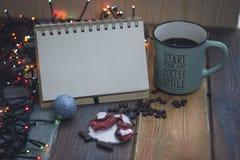 笔记薄,蓝色杯子,圣诞树在桌上的玩具雪人 免版税库存图片
