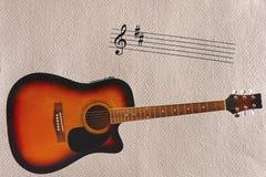 笔记击穿和音响镶有钻石的旭日形首饰的吉他在概略的纸板背景底部  免版税库存图片