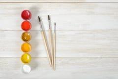 画笔顶视图和与在木背景的五颜六色的树胶水彩画颜料容器 库存照片
