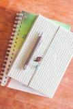 笔顶视图在两个笔记本的在木桌上 图库摄影