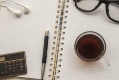 笔,咖啡,流动玻璃,耳机,计算器,投入了笔记本 图库摄影