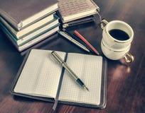 笔,开放笔记本,咖啡杯 免版税图库摄影