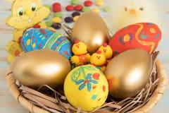 符号复活节归因于在一个篮子的鸡蛋与黄色婴孩鸡、兔子和甜点复活节概念 图库摄影